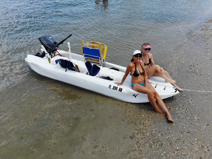 2 girls sitting on a Wavewalk S4 skiff, Florida