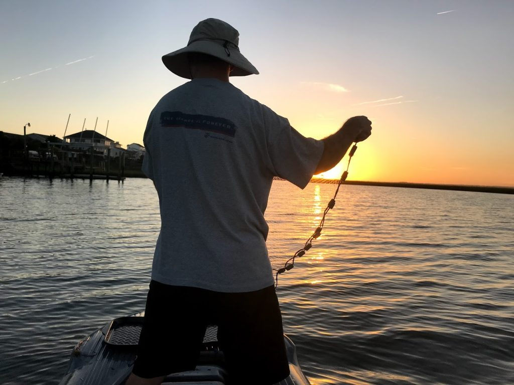NC fisherman casting a shrimping net standing in his S4 skiff